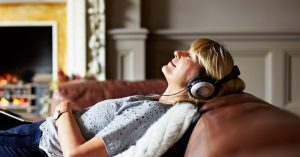 A woman is relaxing on a couch while listening to music