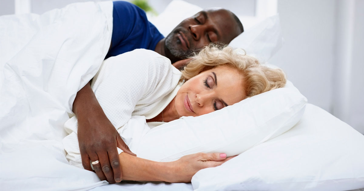A soundly sleeping couple cuddling together