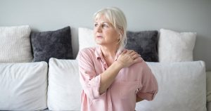 Senior lady with back pain sitting on couch