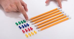 Person's hand arranging pencils and multi-colored pushpins