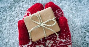 Red mittens holding a small wrapped gift