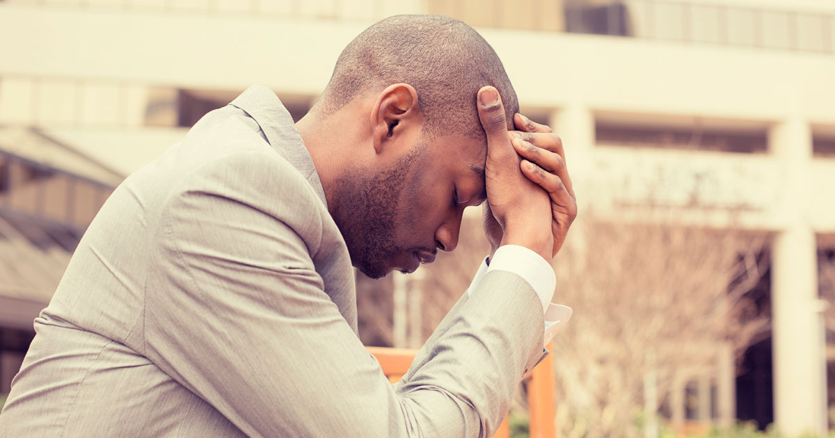 A man is looking stressed while holding his head with his hands