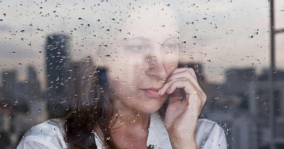 Women is looking outside of window while it rains