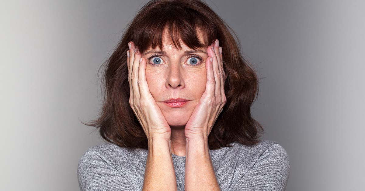 A woman looks distressed while holding her head with her hands