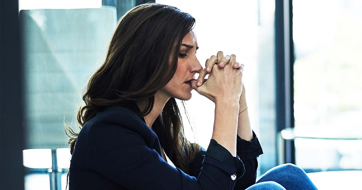A woman is biting her nails anxiously at work